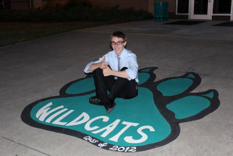 Sitting on the Wildcat footprint at high school before graduation