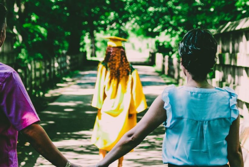 Parents holding hands as daughter walks away in graduation cap and gown